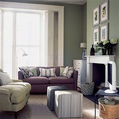 This green living room has orange and purple accents throughout the