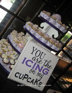 Purple Wedding Cupcake Tower by Cupid Cupcakery. Wedding cupcake tower packed with mini cupcakes, each decorated with lavender flowers and a single jumbo cupcake on top, instead of the traditional cutting cake.