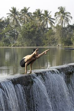 Mariela Cruz in Tittibhasana - yoga balance on top of waterfall - palm trees and sunshine
