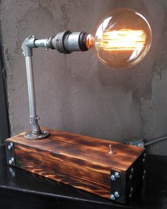 This steampunk lamp is a clever bit of industrial furniture. The wood has a handsome finish and contrasts with the steel in an interesting and effective way. It would make a great desk or table lamp in any industrial setting. Find more designs by November Reserve on their etsy. https://www.etsy.com/shop/NovemberReserve