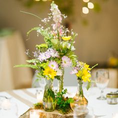 favorite--centerpieces--Make This Look!   Flowers By: Joy ♦ Palm Bay, FL      Looking like the overgrown garden of my dreams, this bride featured an array of textures, heights, and blooms for the perfect fresh-picked look. Clusters of Daisies, Spray Roses, Larkspur, and Button Poms will stand out against the soft Fern greenery, which serves as a delicate, lush background. Creating a wildly romantic look couldn't be easier with this bride's choice of flowers!