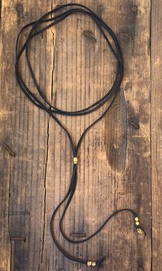 "Bolo style leather wrap necklace. African brass slide bead & faceted brass accent beads. Length 60"" Handmade"