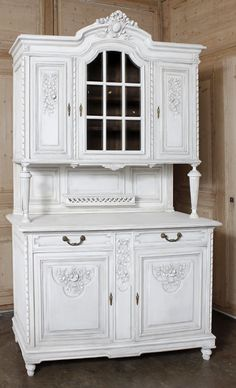 An elegantly ingenious answer to three important requirements, the French china buffet has endured as a most desirable acquisition by those in the know. This particular example, rendered from fine French walnut in the manner of Louis XVI boasts nine glazed panes for display flanked by two crystal cabinets carved with floral and foliate motifs, all directly underneath the arched crown fitted with a lavishly carved cartouche.