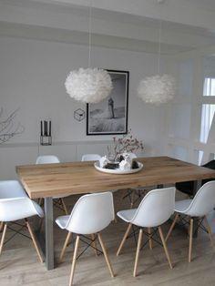 chaises en plastique blanc, table en bois clair, lustre boule blanc, sol en parquet clair
