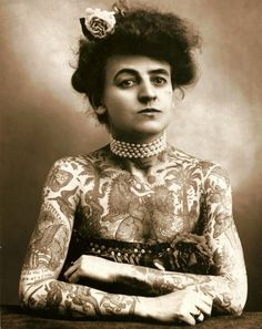 "Maud Wagner (1877-1961) was the first known professional female tattoo artist in the U.S. She became so, writes Margo DeMello in her history ""Inked"" while ""working as a contortionist and acrobatic performer in the circus, carnival, and world fair circuit"" at the turn of the century.  She learned to tattoo from her husband Gus Wagner, an artist she met at the St. Louis World's Fair, who offered to teach her in exchange for a date. Her daughter Lovetta also became a tattoo artist."