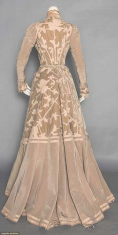 """VELVET & WOOL AFTERNOON GOWN, c. 1902. 2-piece, taupe moire silk faille & velvet w/ faun wool flannel appliques in stylized folige motifs, bolero style bodice, high neck """"under bodice"""" of cream silk panne, ribbon embroidered & lace trimmed lapels, lace jabot. Back"""