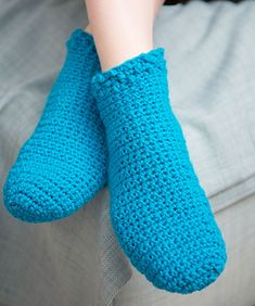 Wool-blend crocheted socks are perfect to keep your feet warm as you relax at home. The design around the top of the sock adds a fun touch.