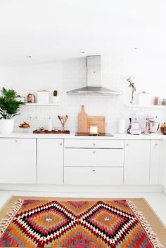 Love this all-white kitchen space with pops of color from the patterned rug, mini potted palm and pink Cuisinart standing mixer!