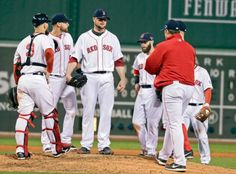 Boston Red Sox manger John Farrell, right, reaches the mound to relieve starting pitcher Jon Lester, center, in the middle of the 7th inning. (Charles Krupa/AP)
