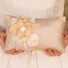 Le coussin à alliances rustique en toile de jute décoré de jolies fleurs en tissu et de dentelle