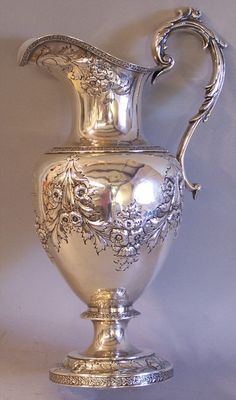 J E Caldwell Co antique sterling silver water ewer signed P L K Standard. Weighs 930 grams and measures 14 inches tall.Monogrammed with an engraved  boars head, hand and E M E. Master hand work depicting flowers and vines. The perfect decorative vase for flowers.