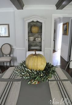 Putting a wreath with a pumpkin on top of it on top of a cake stand makes for a very simple and easy fall centerpiece. We added some striped placemats from @homegoods to finish off the space. (sponsored pin)
