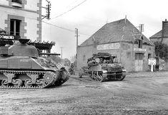 30 juillet 1944 à Saint-Martin-des-Besaces, un convoi de la 8th Rifle Brigade passe le carrefour de la route Villers-Bocage / la Ferrière-Harang, le Sherman du premier plan appartient au 23rd Hussars britannique. (Imperial War Museum/B8292).