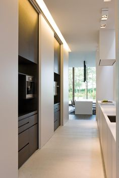 Elegant custom kitchen by Minus architects with large sliding panels