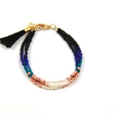 """Triple strand of delica, czech glass seed beads, and gold plated beads finished with a cotton tassel.This bracelet is 7.5"""" with an extender chain to fit any wrist comfortably.>>> <<< >>>"""