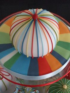 Fondant multi color base with a royal icing ribbon round cake.