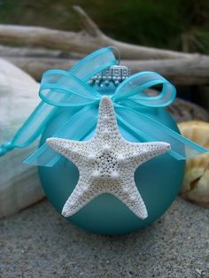 Beautiful tiffany blue frosted glass ball ornament decorated with a cute white knobby starfish. Ribbon is a lovely, matching tiffany blue with