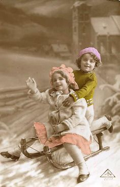 Vintage tinted Victorian-era postcard with two children in the snow