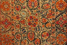 SUZANI, UZBEKISTAN, 19th C. Silk embroidery on cotton, five joined panels decorated in pumpkin, blue, purple and green silk with flowers and vinework, Ikat trim on verso, five velvet tabs attached for hanging. 53 x 90. (1 x 1 inch dark brown stain top center) otherwise excellent.
