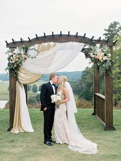 Bride And Groom Share A Kiss Under Rustic Wedding Arch
