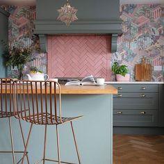 Pink herringbone tiled splashback, copper metal bar stools, green kitchen units and green and pink wallpaper in the kitchen #kitchenideas #kitchen #kitchendetails #wallpaper #herringbone
