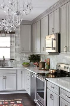 Gray kitchen features gray raised panel cabinets paired with Viatera Snow Storm Quartz countertops and a gray polished marble subway tile backsplash.