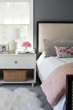 Gorgeous bedroom boasts a white one-drawer open nightstand positioned on a gray hexagon rug layered beneath a white sheepskin rug and beneath a window dressed in a white roman shade.
