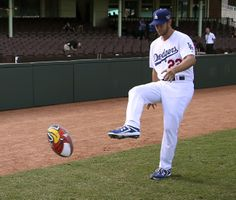 The Los Angeles Dodgers' Clayton Kershaw kicks a rugby league ball at the Sydney Cricket Ground in Sydney, Wednesday, March 19, 2014. The MLB season-opening two-game series between the Dodgers and Diamondbacks in Sydney will be played this weekend. (AP Photo/Rick Rycroft)