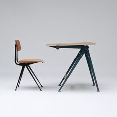 Drafting table and chair by Wim Rietveld & Friso Kramer    Drafting table and desk by Wim. Rietveld & Friso Kramer won the Signe D'Or in Brussels. Mult-functional and iconic this piece can used as a standing drafting table or when folded in the center functions as a normal working desk height unit.