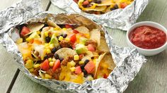 Turn to the grill for a fun way to heat and serve nachos, with foil packets holding chips, prepared meat sauce, cheese, and more.