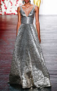 This sleeveless **Naeem Khan** ball gown features allover gunmetal beaded embroidery with a plunging v-neckline and a fitted bodice.