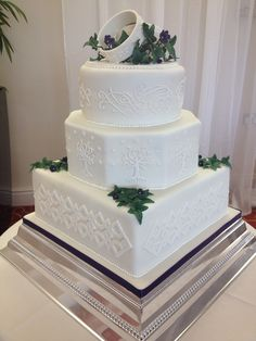 "Lord of the Rings inspired wedding cake. Inspiration for Base tier - Killi's cloak trim.  Centre tier - White Tree of Gondor.  Top tier - Arwen's Dress sleeve embroidery.  The Rings are embellished with the quote from the Film - ""I would rather share one lifetime with you than face all the ages of this world alone""  - written in Elvish script."
