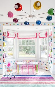 Colorful playroom with a Rainbow chandelier by Sazerac Stitches, a play table with pink and green acrylic chairs, polka dot wallpaper, and rainbow shelves filled with books that are arranged by color. Rainbow Room Kids, Rainbow Wall, Lucite Chairs, Kids Room Lighting, Colorful Playroom, Acrylic Chair, Baby Boy Nursery Decor, Modern Lighting Design, Chandelier