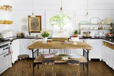 Wood accents (open shelving, kitchen island) in varying tones warm up the all-white palette. Cindy found the vintage table at Bill Moore Antiques in Round Top and repurposed it as an island in the kitchen.
