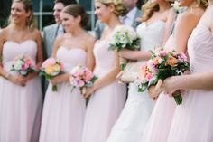 Bridesmaids carry bouquets with an array of pink and orange flowers at an elegant wedding hosted at the Historic Barns of Nipmoose. Mary Dougherty Photography, The Posie Peddler