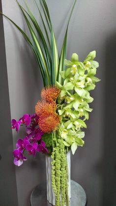 Pin cushion protea, trick, hanging amaranthus, cymbidium & phal orchids in a