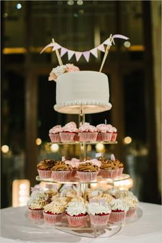Cupcake tower topped with a wedding cake @weddingchicks