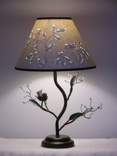 Another lampshade design choice for the Bird and Berry Table Lamp. When the light is off, your shade looks like a plain cream paper lampshade. But when you turn your light on, the cut and pierced lampshade features a pair of black capped chickadees sitting on a branch with green leaves and red berries which compliments the metal finished lamp base. The lampshade is reverse painted on cream paper with a special flecked lining which only becomes visible when the light is on. The shade is…