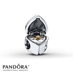 Shaped like a jewelry box and decorated with a trail of hearts on the top and bottom, this sterling silver Gift from the Heart charm from the 2014 Valentine's Day collection by Pandora opens to reveal a surprise – a tiny 14K yellow gold ring accented with clear cubic zirconia center. Style # 791247CZ.