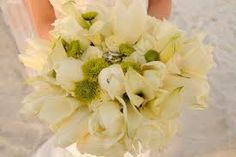 This gorgeous white bridal bouquet is absolutely perfect for a beach wedding with white roses, calla lilies, tulips and lilies.