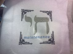 """Chai Maintenance""    Three colors: Black filigree framework, blue & silver blended thread for ""maintenance"" & a textured silver metallic chai on white glitter felt. 29,937 stitches in all.     ""Chai Maintenance"" is what it says. The Hebrew ""Chai"" symbol of Judaism (the letters Chet-Yud). The word Chai (חי) means ""living"" in Hebrew & is related to the word for ""life"", Chaim. So, it's a double play on words for my daughter Anna, an educator & now the director of a synagogue school. :)"