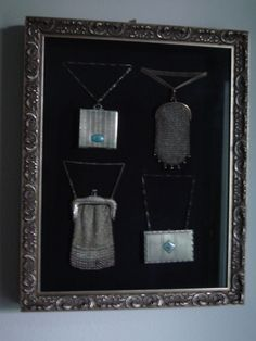 Antique change purses and compacts in a shadow box