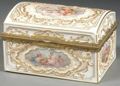 Year: 1830 - 1870 A French porcelain jewelry casket, mid 19th century, rectangular, with slightly domed lid, embossed with rocaille and scroll cartouches enclosing classical scenes of goddesses and attendants, gilt detailing, gilt-metal rim.