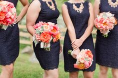 Navy bridesmaids dresses with coral accents.