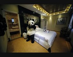 An employee dressed in a panda costume poses for a photo during the soft opening of a panda-themed hotel at the foot of Emei Mountain, Southwest China's Sichuan province, on Feb. 25 2013.