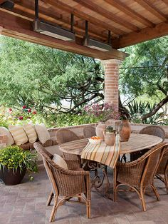 Tuscan Touch - A Tuscan-style table is paired with weathered wicker chairs. The curved edges of the table legs and chairbacks help to make the pieces feel cohesive. A low built-in bench increases seating in this outdoor dining area. A brick pillar helps to support the porch roof and adds a bit of visual interest to the space.