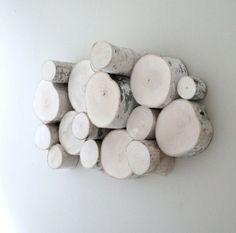 originelle Deko aus kleinen Birkenstämmen an der Wand