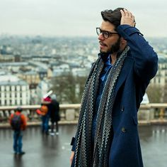 Kadu Dantas in a long coat and unwrapped chevron print scarf during PFW