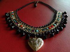 Confeccionado com corrente dourada e preta, fio de strass colorido, cristais pretos e pingente de coração dourado. R$ 100,00
