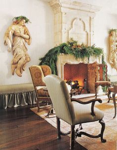 """""""An 18th-century limestone fireplace surround flanked by 17th-century wooden angels. Venetian 18th-century canape and French 19th-century wing chair both"""